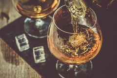 Gietende cognac in een glas royalty-vrije stock afbeeldingen