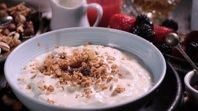 Gietende graangewassen over een kom yoghurt voor ontbijt met bessen en droge vruchten stock video