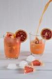 Gietende grapefruit juice in een glas op witte achtergrond Royalty-vrije Stock Afbeeldingen