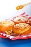 Gietende honing achter verse kaneelbroodjes Royalty-vrije Stock Afbeeldingen