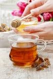 Gietende honing in glas thee Stock Foto's