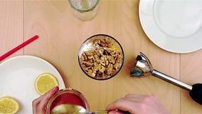 Gietende honing over okkernoten in de mixer voor een gezonde en voedzame smoothie stock footage