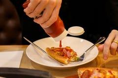 Gietende ketchup aan de kaaspizza Royalty-vrije Stock Foto's