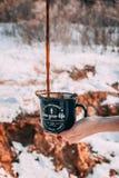 Gietende koffie aan de blauwe kop royalty-vrije stock afbeeldingen