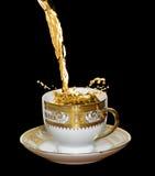 Gietende koffie in de kop, die op zwarte wordt geïsoleerdo Stock Foto