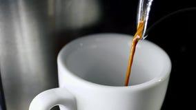 Gietende koffie in kop van elektrische koffiemachine die in 4k resolutie in langzame motie schieten stock video
