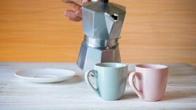 Gietende koffie in koppen bij de keuken stock videobeelden