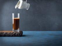 Gietende koffie in lang glas op donkere achtergrond Stock Fotografie