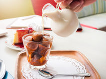 Gietende melk aan glas vorstthee stock afbeelding