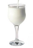 Gietende melk in een wijnglas Stock Fotografie