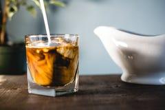 Gietende melk en koffie in een glas stock afbeelding