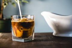 Gietende melk en koffie in glas stock foto's