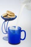 Gietende melk en ongezuurde broodjes. Stock Foto's