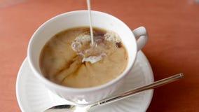 Gietende melk in hete zwarte thee in witte kop stock videobeelden
