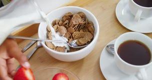Gietende melk in kom van cornflakes stock videobeelden