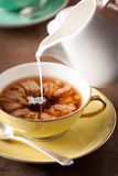 Gietende melk op een theekop Stock Foto