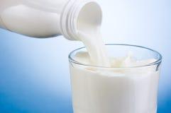 Gietende melk van witte plastic fles in glas op blauw Royalty-vrije Stock Afbeelding