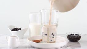 Gietende melkthee in glaskop met de smakelijke populaire bel van de de tapiocaparel van Taiwan op heldere marmeren lijst en wit d stock footage