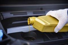 Gietende motorolie in een motor van een auto stock afbeeldingen