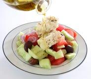 Gietende olie op Griekse salade stock afbeeldingen