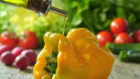 Gietende olijfolie over een groene paprika stock video
