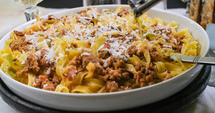 Gietende olijfolie over heerlijke fettuccine in bolognese saus Stock Foto's