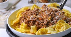 Gietende olijfolie over heerlijke tortellini in bolognese saus Royalty-vrije Stock Foto's