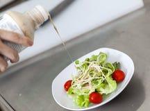 Gietende saladesaus op de salade van de zonnebloemspruit Stock Afbeeldingen