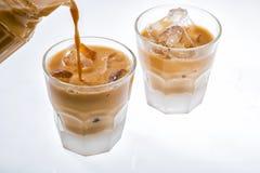 Gietende thee aan glas met ijs stock fotografie