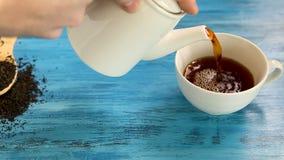 Gietende thee in een witte kop stock video