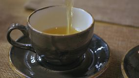 Gietende thee van theepot in uitstekend ceramisch theekopje stock video
