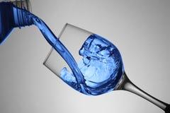 Gietende vloeistof in de drinkbeker royalty-vrije stock foto