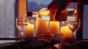 Gietende wijn in glazen op een achtergrond van de stad bij nacht met bokeh en braadstukvissen op vakantielijst 1920x1080 stock videobeelden