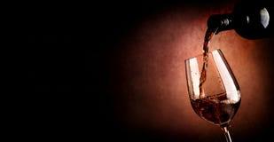 Gietende wijn op bruin Royalty-vrije Stock Afbeeldingen
