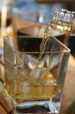 Gietende wisky in het glas Stock Foto's