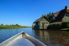 Giethoorn canal and beautiful cottages on shore. Royalty Free Stock Photography