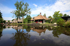 Giethoorn. A cottage with a thatched roof in the village of Giethoorn in The Netherlands during a beautiful summer morning Stock Images