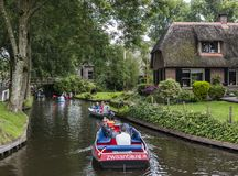 Boats in Canals in Giethoorn. Giethoorn, The Netherlands - August 16, 2016: Boats in the canals of the small, picturesque town of Giethoorn with old monumental stock images