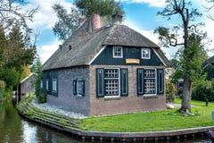 Giethoorn wioska z kanałami i wieśniacy pokrywającymi strzechą dachów domami w rolnym terenie fotografia royalty free