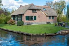 Giethoorn wioska z kanałami i wieśniacy pokrywającymi strzechą dachów domami w rolnym terenie obrazy royalty free