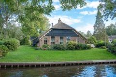 Giethoorn wioska z kanałami i wieśniacy pokrywającymi strzechą dachów domami w rolnym terenie obrazy stock
