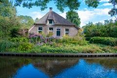 Giethoorn wioska z kanałami i wieśniacy pokrywającymi strzechą dachów domami w rolnym terenie obraz stock