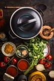 Gietijzerpot met verse ingrediënten voor smakelijke vegetarische tomatensoep of saus die koken: de tomaten, kruiden, kruiden, bli stock foto's