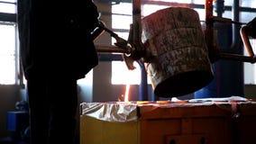 Gietijzeruitsmelting De arbeiders gieten gietijzer van capaciteit in een speciale vorm uit Het gesmolten gietijzer stock footage