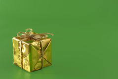 Gift. Gold christmas gift on the green background stock images