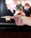 Gift. Hand holding out an envelope on blurred backg Royalty Free Stock Photos