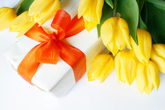Gift. A white chocolate box surrounded by yellow tulips Stock Photography