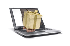 Gift. A Hand reaches out of an Laptop with a gift Stock Images