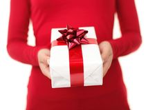 Gift. Christmas gift. Woman giving / holding christmas present. Focus on the gift - shallow depth field. unrecognizable person isolated on white Stock Photo