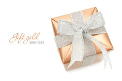 Gift. Gold box with silver ribbon on white background. Copyspace Royalty Free Stock Photos